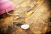 Pink heart locket, a wood background. — Stock Photo