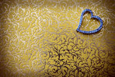 Elegant heart-shaped jewelry in gold-colored background. — Zdjęcie stockowe