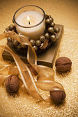 Festive candle surrounded by nuts and tape. — Stock Photo