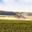 Farm tractor spraying a field. — Stock Photo #48165505