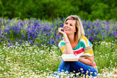 Young attractive girl studying in a flowery meadow. — Stockfoto