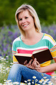 Blonde girl reading the flowery meadow. — Stock Photo