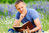 A man reads a book in the field. — Stock Photo