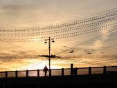 Muž chodí přes most při západu slunce — Stock fotografie
