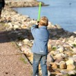 Boy playing on the river bank with a sword — Stock Photo