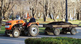 Orange tractor with a trailer park — Stock Photo