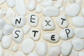 Next step words on pebbles — Stock Photo