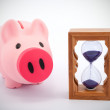 Piggy bank and hourglass — Stock Photo #18098619