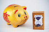 Piggy bank and hourglass — Stockfoto