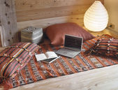 Computer and pillows on the red carpet in the rustic living room — Stock Photo