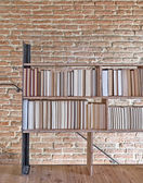 Modern bookcase overlooking on the brick wall — Photo