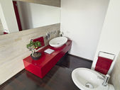 Modern bathroom with red cabinet — Stock Photo