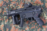 German modern submachine gun MP5 on camouflaged background — 图库照片