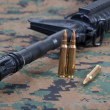 Stock Photo: M4A1 carbine with cartridges on us marines camouflage uniform
