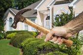 Ruka držící kladiva v přední části domu — Stock fotografie