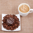 Coffee with milk on sacking,a saucer with a coffee bean and choc — Stock Photo