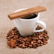 Stock Photo: Cinnamon sticks are on cup of black coffee in surroundings