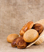 Panary rolls pour out from a basket — Stock Photo