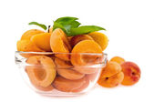 Halves apricot in a dish on a background whole apricot — Stock Photo