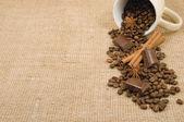 Coffee grain, cinnamon, chocolate and anise on a background sack — Stock Photo
