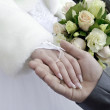 A woman hand with a wedding ring lies in a masculine palm on a background a bouquet — Stock Photo