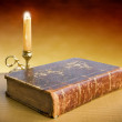 Candlestick and old book lie on a table on a yellow background — Stock Photo