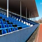 Tribune of stadium with dark blue seats empty — Stock Photo #33659389