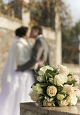Bouquet from roses on a background kissings newly-weds — Stock Photo