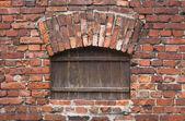 Bakstenen muur met een houten venster — Stockfoto