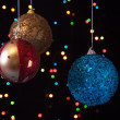 Three Christmas ball on a black background with lights — Stock Photo #33667597