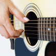 Woman hand plucking strings on a guitar — Stock Photo