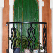 Balcony wooden green door with flowers and forged railings — Stock Photo