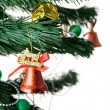 Christmas bell and new year beads on the branch of a tree — Stock Photo