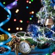 Round pocket watch, Christmas toys, a decorated Christmas tree, serpentine on a black background with lights — Stock Photo