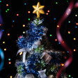 Dressed up fur-tree with the star on top,streamers on a black background — Zdjęcie stockowe