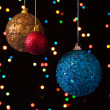 Three Christmas ball on a black background with lights — Stock Photo