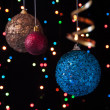 Three Christmas tree ball,serpentine on a black background with lights — Stock Photo