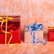Three gift boxes on an orange background — Stock Photo #33667781