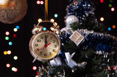 Clock ,a decorated Christmas tree on a black background with lights — Stock Photo