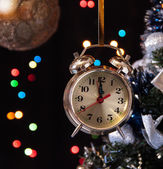 Clock and decorated Christmas tree on a black background with lights — Stock Photo