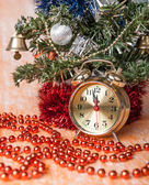 Clock,Christmas beads on the background of decorated Christmas trees — Stock Photo