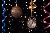 Horloge, serpentine, boule de noël sur fond noir avec des lumières — Photo