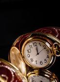 Runde goldene uhr mit einem maßwerk roter schleife auf schwarzem hintergrund — Stockfoto