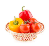 Tomatoes and peppers in a wicker basket on a white background — Stock Photo