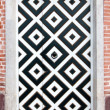 Door into a brick wall with white and black squares ornament — Stock Photo