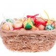 Easter eggs in a straw basket on the white — Стоковая фотография