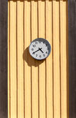 Clock on the wooden yellow wall — Stok fotoğraf
