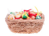 Easter eggs in a straw basket on the white — Stock Photo