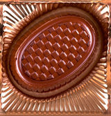 Chocolate candy lies in the cell box macro — Stock Photo