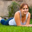 Smiling woman lying outdoors — Foto Stock